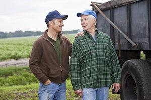 Farmers standing beside truck, potato field in background.
